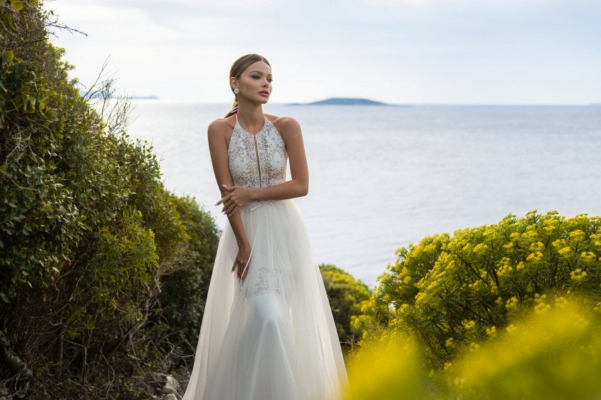 "An elegant wedding set in a trendy ""boho"" style, which consists of a light dress on the straps and a removable skirt with a train. Dress with a translucent bodice with original ties on the neck. Original skirt, tight-fitting figure, with a figured insert above the knee. A light look will become a real decoration of a summer wedding."