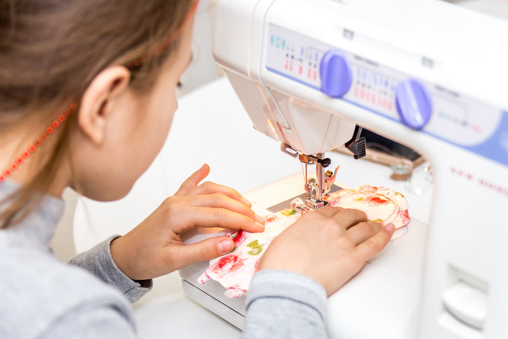 Girl sewing on a sewing machine