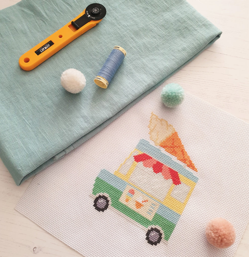 sewing materials and a cross stitch embroidery