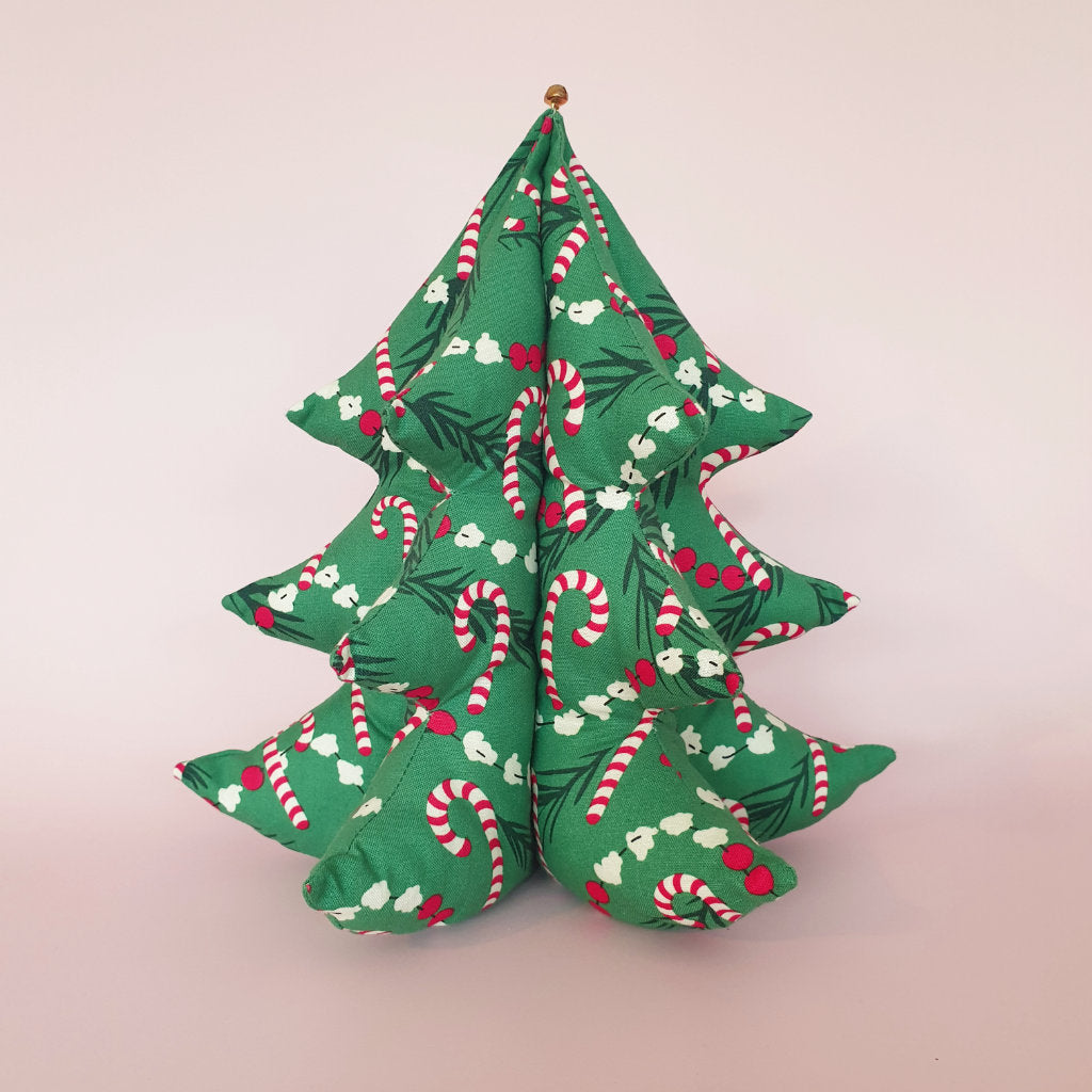 A handmade fabric Christmas tree sits on a pink background. The festive fabric features popcorn and candy canes strung on the tree.