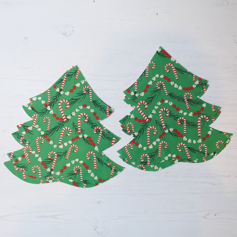 several christmas tree shapes cut out from fabric