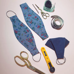 flat lay on pink background showing handmade masks and sewing tools