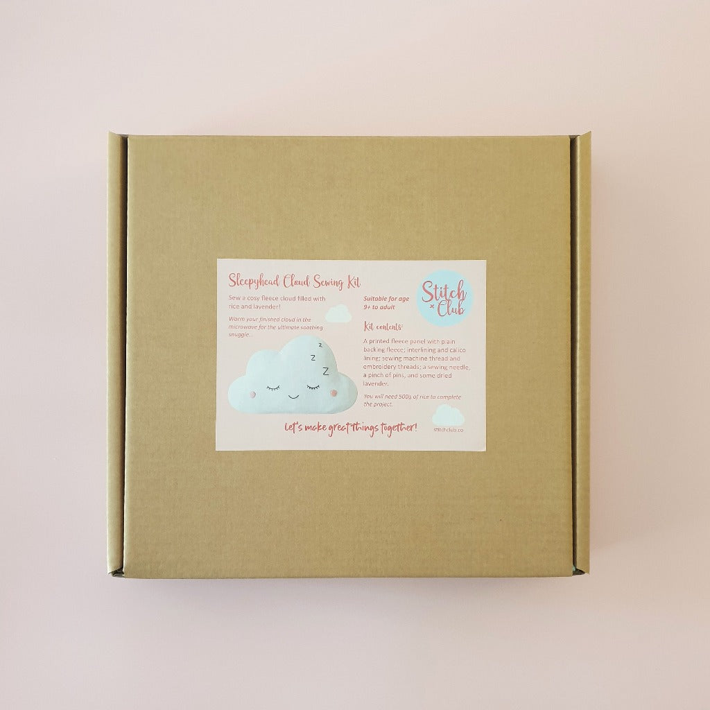 A cardboard box containing supplies for a sewing kit, to make a fleecy kawaii cloud with an embroidered sleepy face.