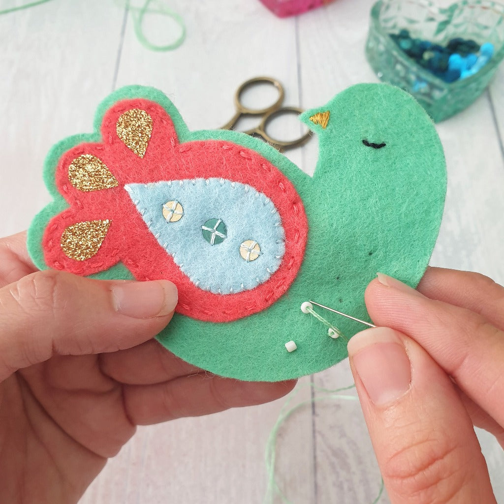 A felt partridge Christmas decoration being sewn by hand, with little beads
