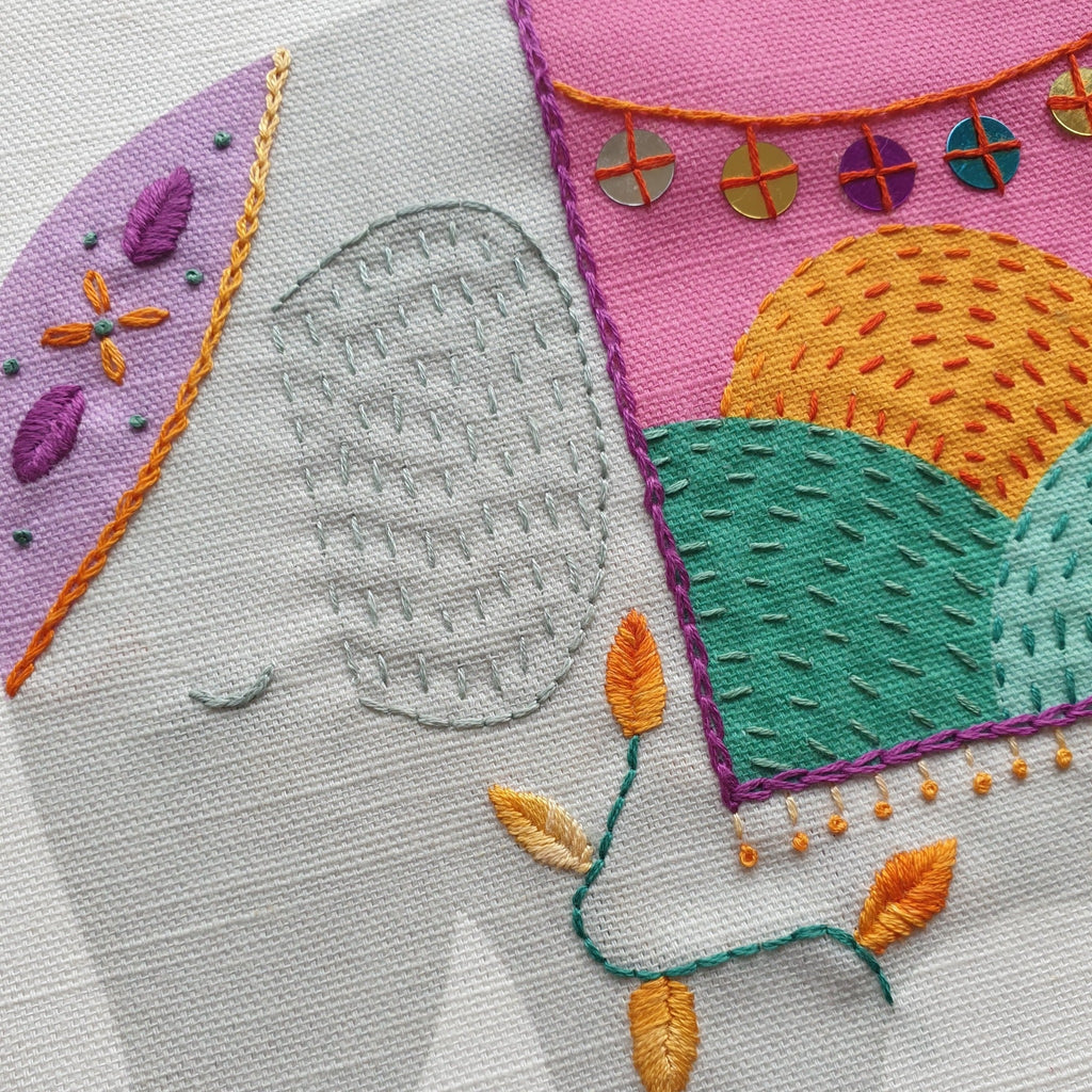 A close up of embroidery on a printed elephant panel, with chain stitch, backstitch, running stitch and french knots.