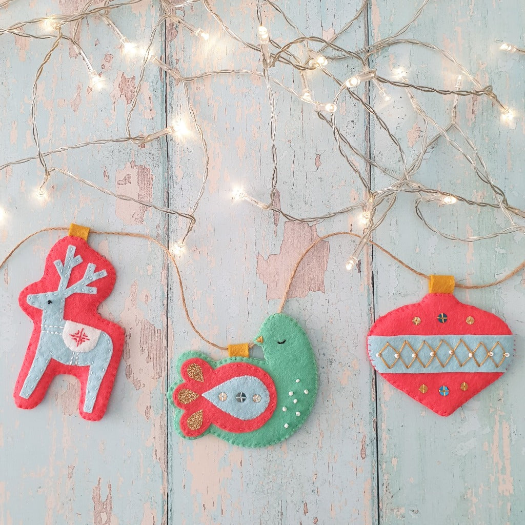 A felt garland of handmade Christmas decorations adorned with fairy lights