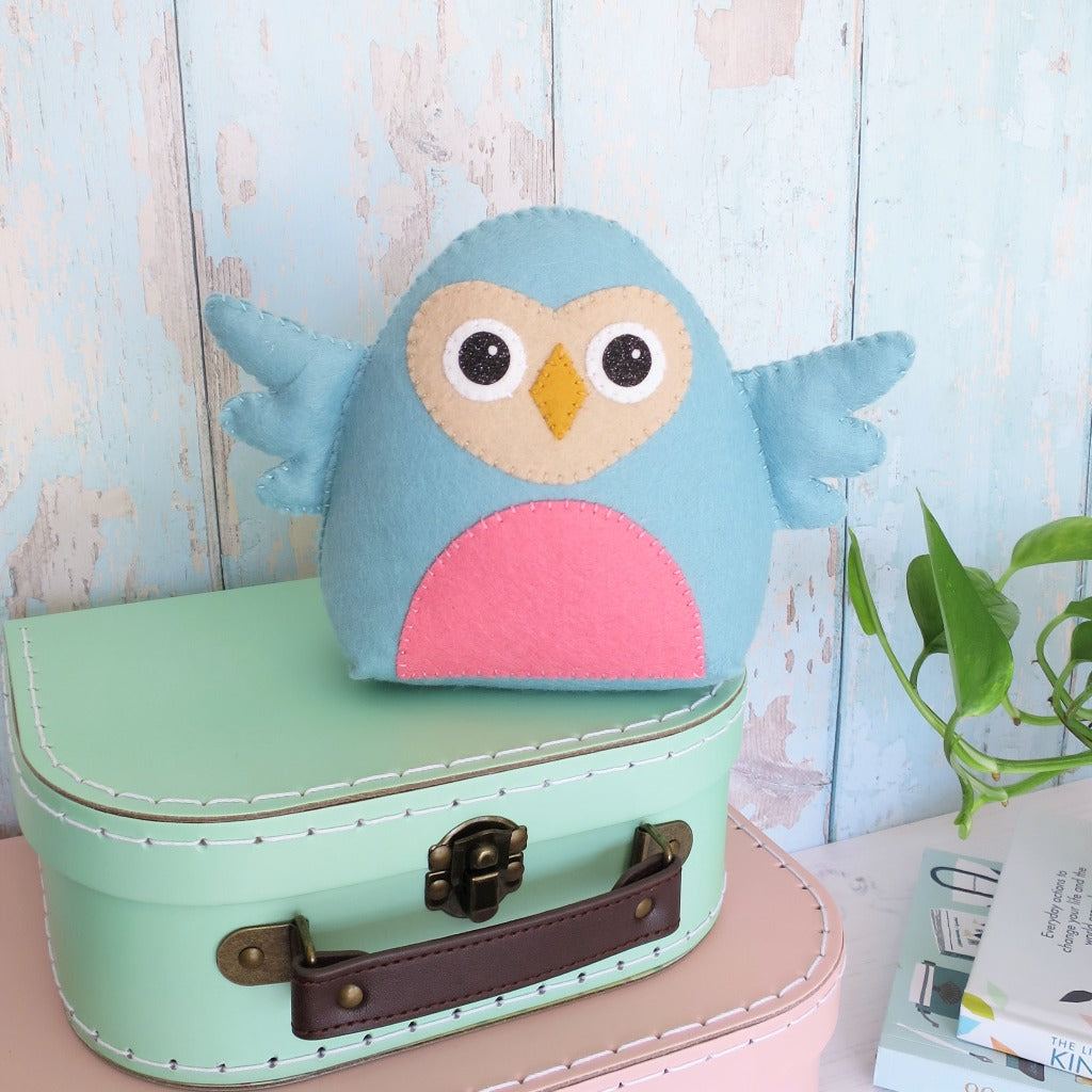 a handsewn felt owl perched on suitcases