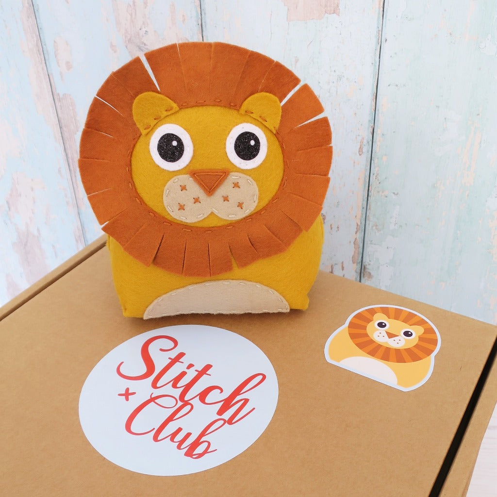 a handmade felt lion toy sits on a sewing kit box
