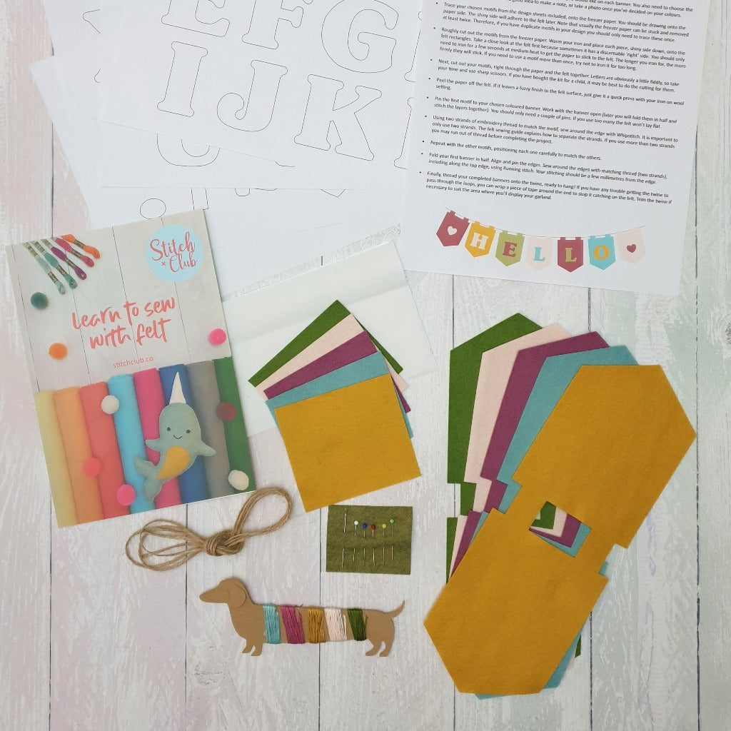 A photo of the contents of a sewing kit, featuring felt banners, threads and pins