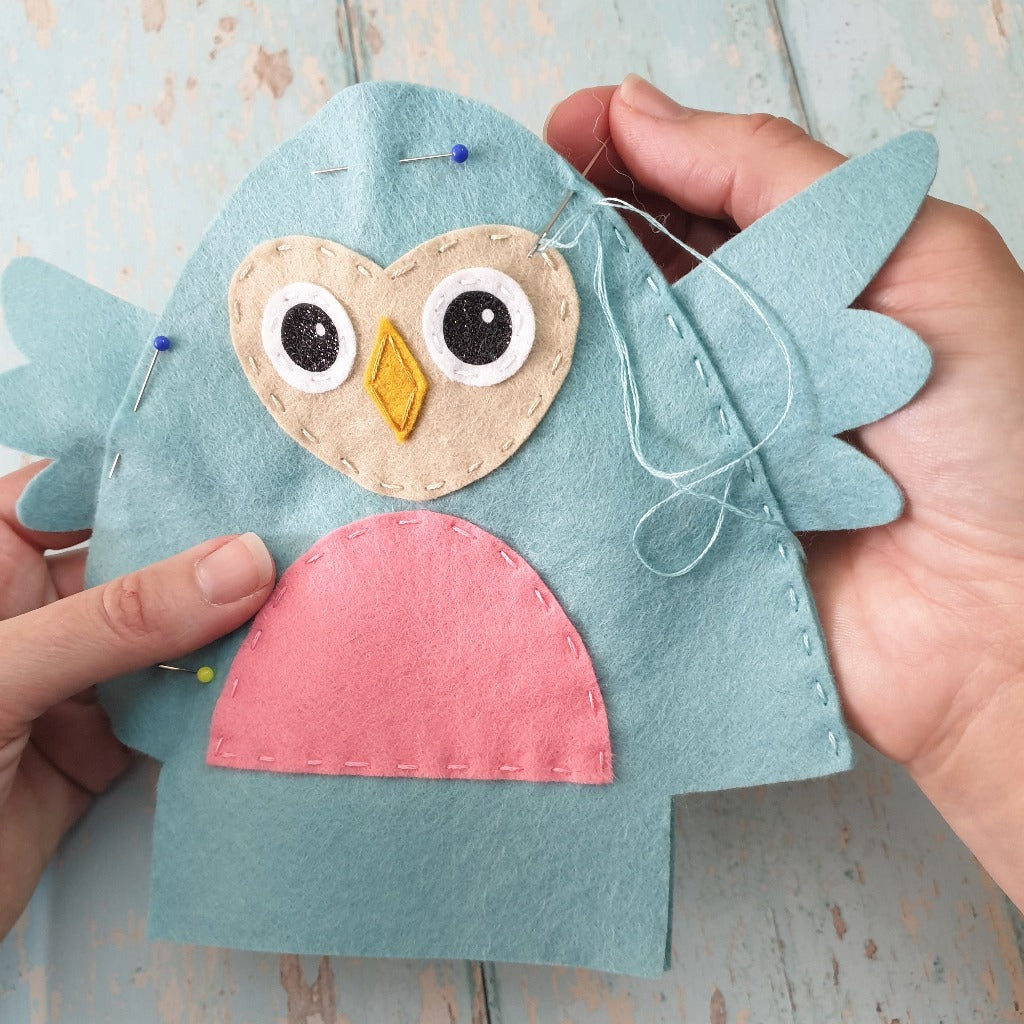 hands sewing a felt owl using running stitch