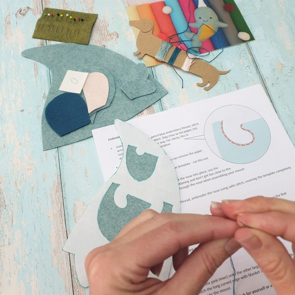 In the foreground, hands are threading a sewing needle. In the background a selection of craft materials are ready to sew into a little blue felt mouse