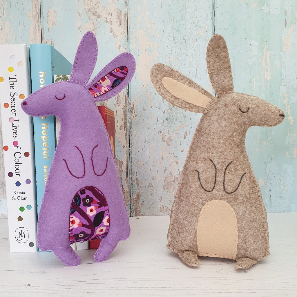two felt hares sewn by hand, sitting on a shelf with some books