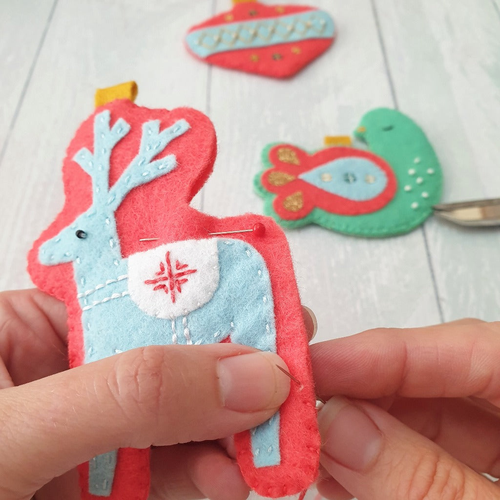 A scandi style felt reindeer being handsewn with felt as part of a Christmas sewing kit