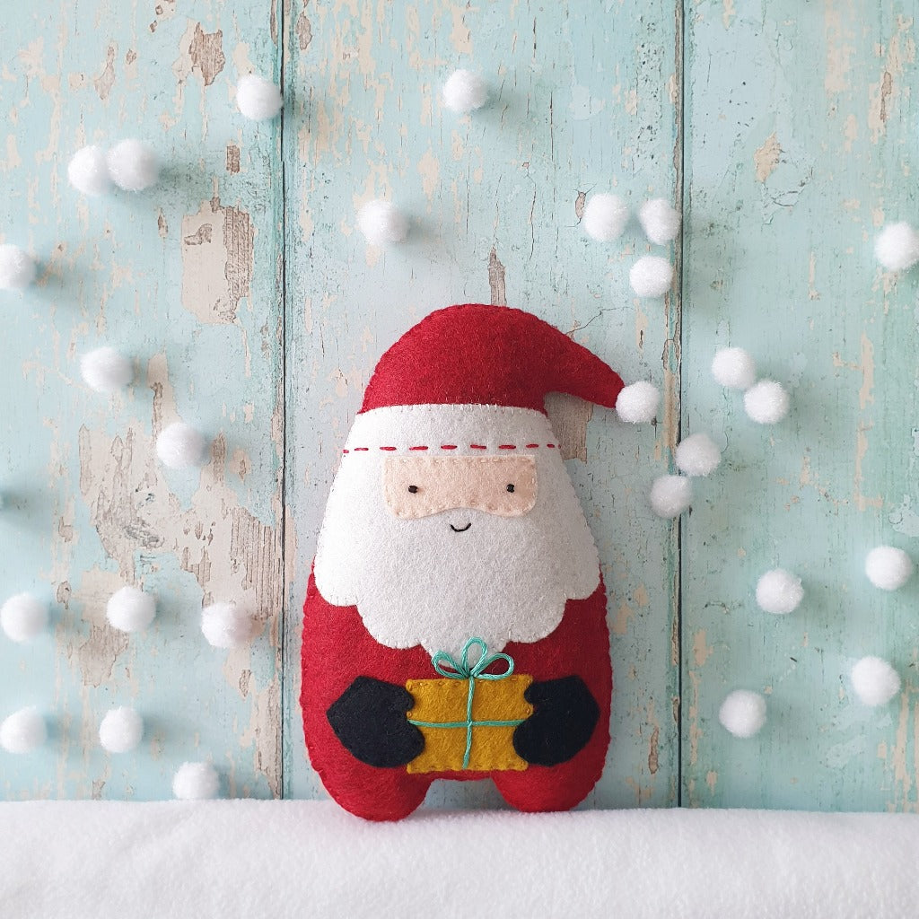handsewn felt santa claus christmas decoration, on a rustic blue background with pompom snow falling around him
