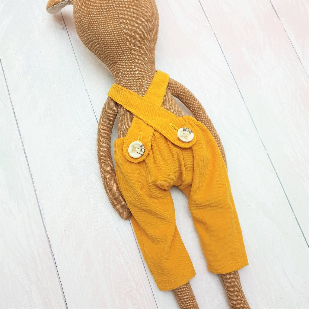 Detail of a Deer soft toy, handsewn, wearing yellow corduroy dungarees with a button back