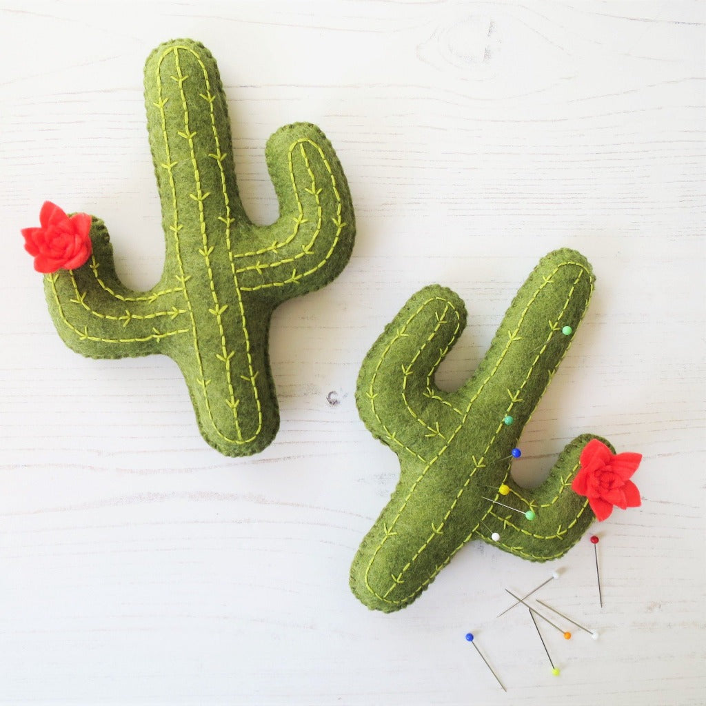 Two felt cacti, handsewn with embroidery stitches and flowers.