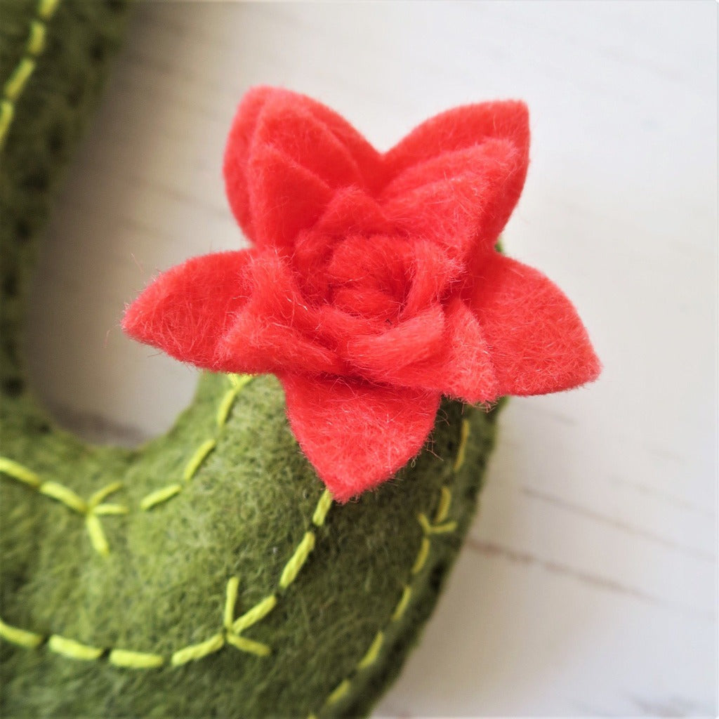 A close up of a coral pink felt flower, attached to a felt cactus.