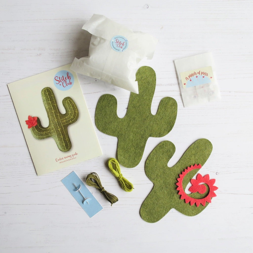 The contents of a felt cactus sewing kit, with threads, die-cut cacti, pins, stuffing, needle and an instruction fold-out manual