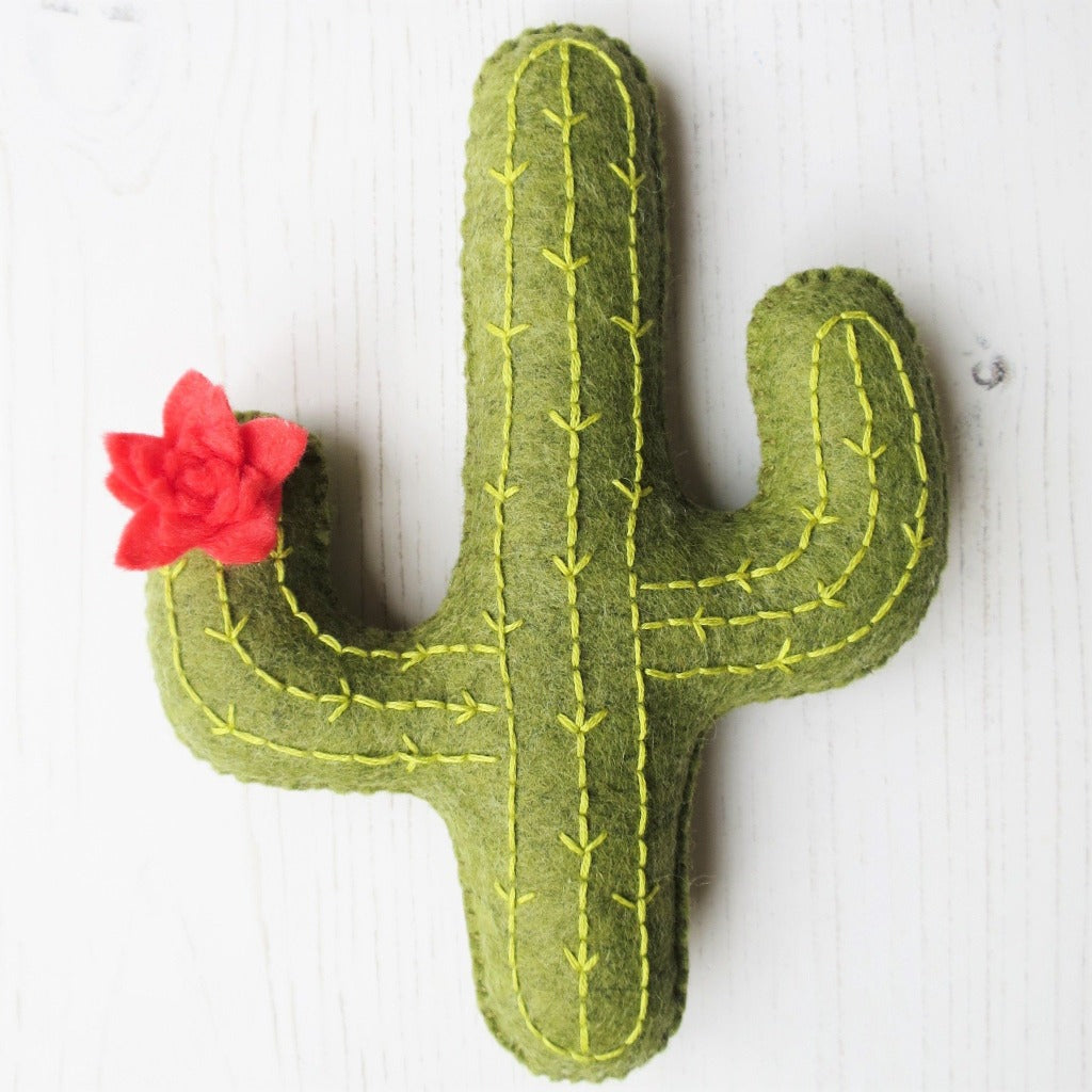 A handsewn felt cactus, with embroidery stitching and and a pink flower.
