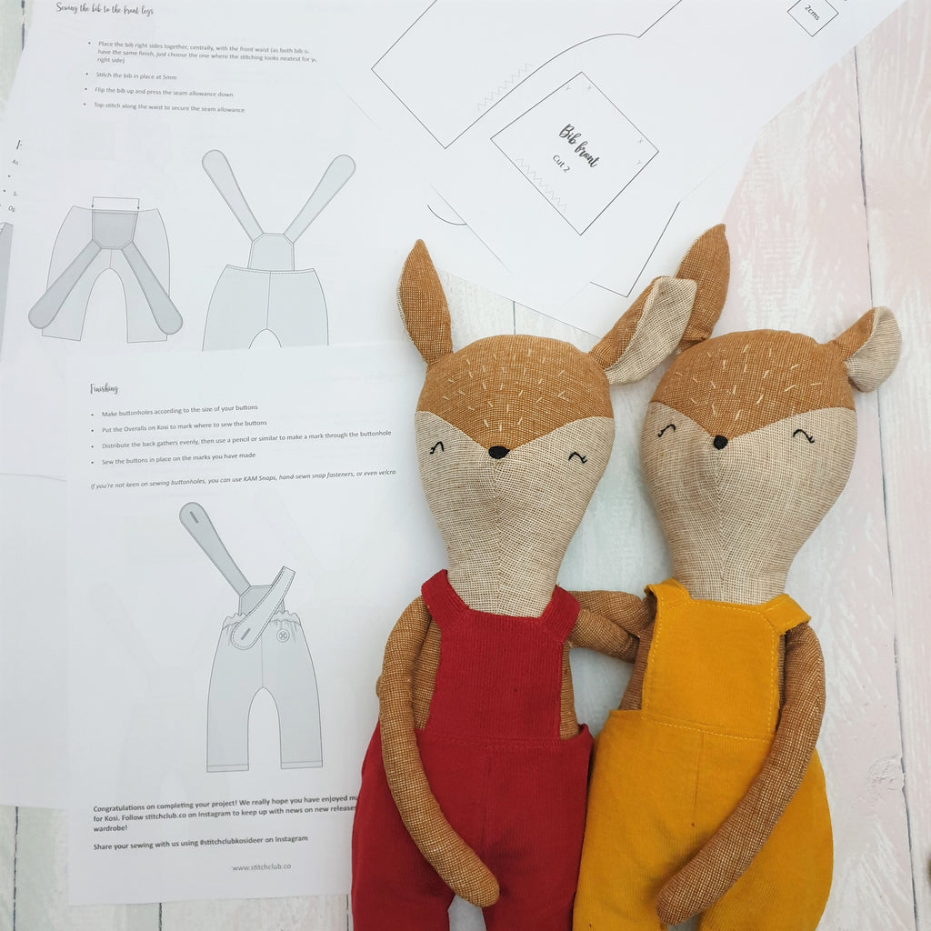 Two vintage style toy deer wearing colourful overalls and surrounded by pages from a sewing pattern