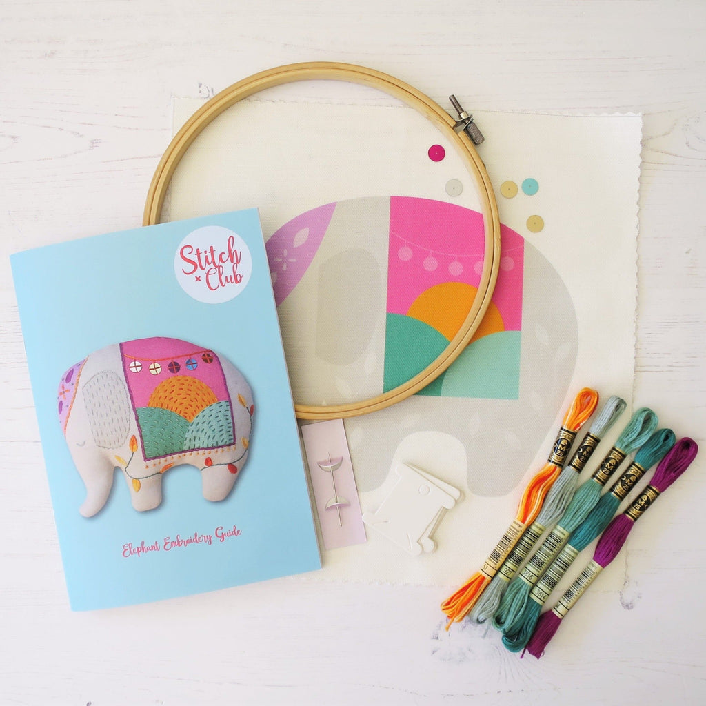 The contents of an embroidered elephant sewing kit, featuring DMC embroidery threads and an embroidery hoop.