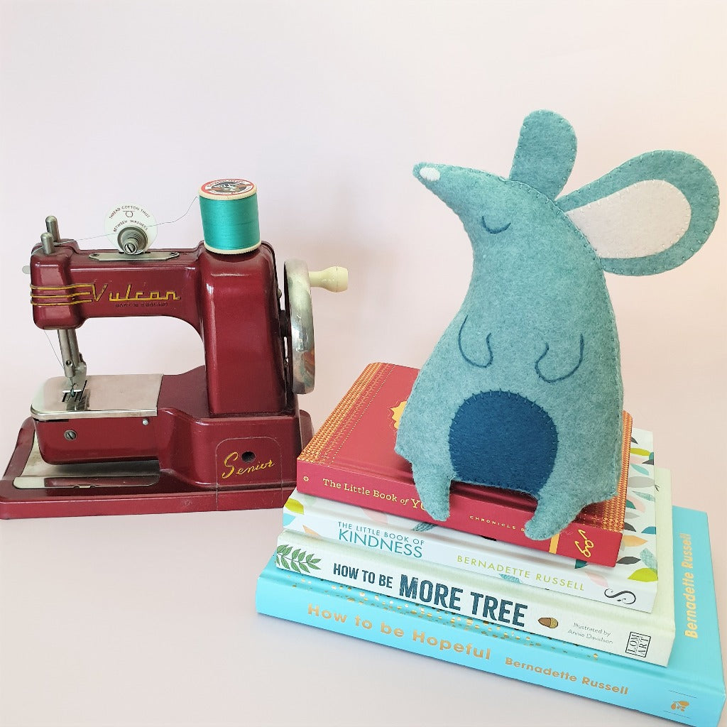A handsewn blue felt mouse perches on a pile of books, next to a vintage Vulcan Senior children's sewing machine from the 1950s