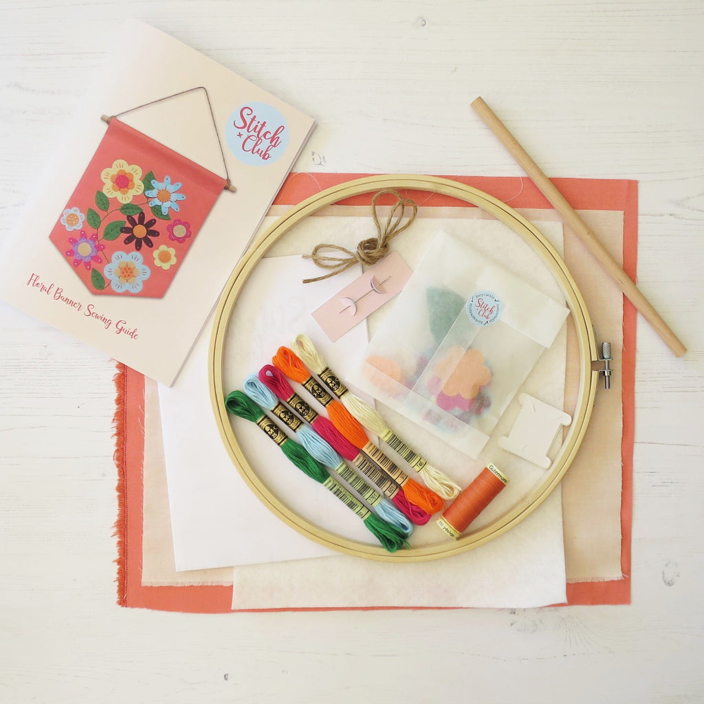 A flat lay showing the contents of this sewing kit. Fabrics, threads and sewing needle, with an embroidery hoop, and a sewing guide booklet