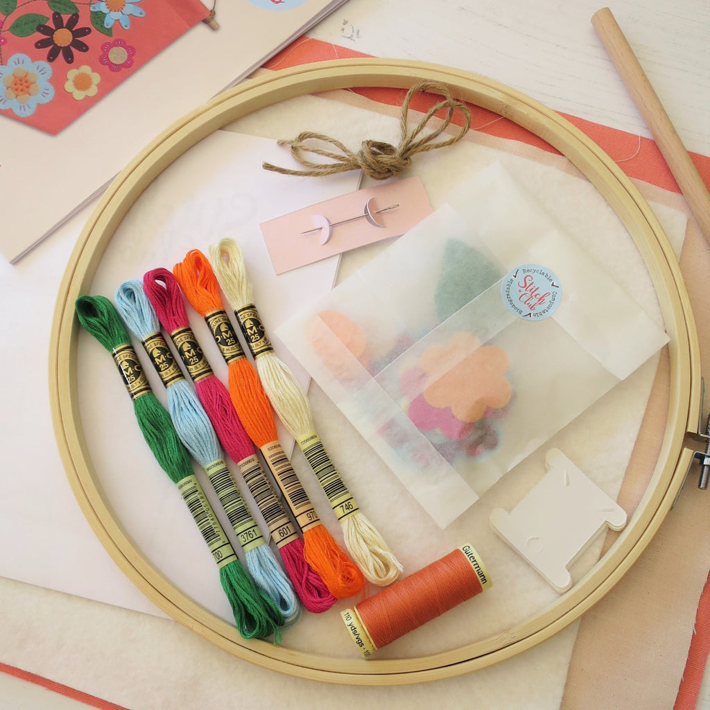 A close up of the sewing kit including a 25cm bamboo embroidery hoop with DMC cotton embroidery threads and other sewing kit supplies