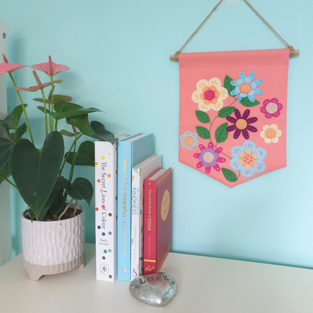 A colourful handsewn applique banner, decorated with felt flowers, hangs on a turquoise wall. On a surface in front, sits a plant and some books.
