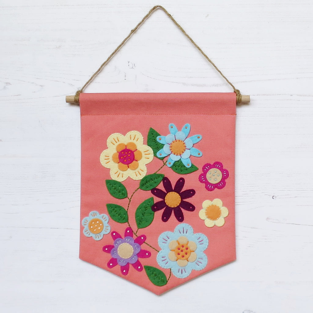 A pinky-orange canvas penant banner hanging from twine. Hand sewn applique felt flowers with embroidery stitches.