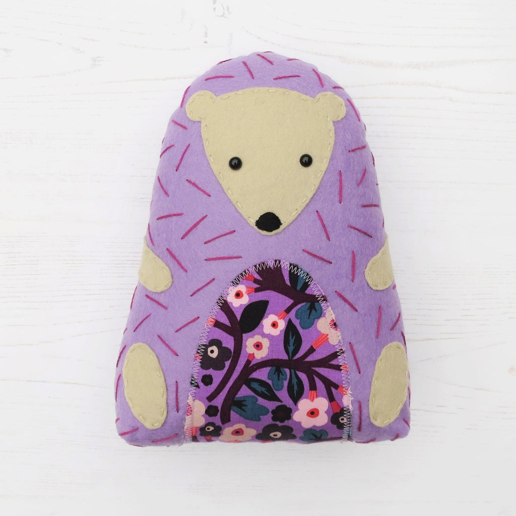 A handmade purple lilac felt hedgehog, with a floral tummy, zig-zag stitching, and hand embroidery.