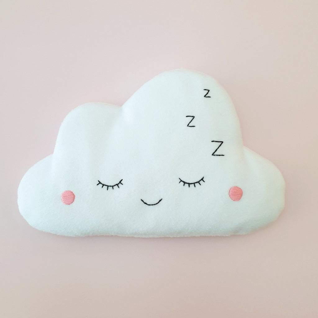A fluffy white cloud sewn from fleece has an embroidered sleepy face. It is filled with rice and lavender, to be warmed in the microwave.