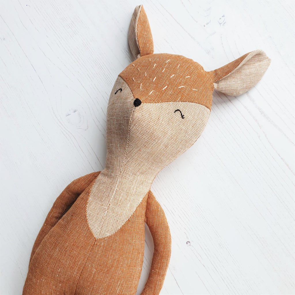 A close up of a vintage style handmade toy deer, featuring home-spun essex linen fabrics.