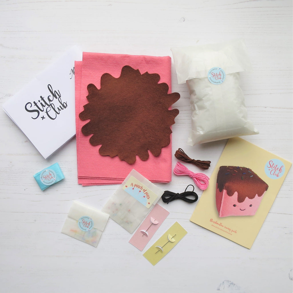The contents of a hand sewing kit, including felt pieces in pink and brown, embroidery threads, pins, needles, stuffing and a sewing guide with a paper pattern.