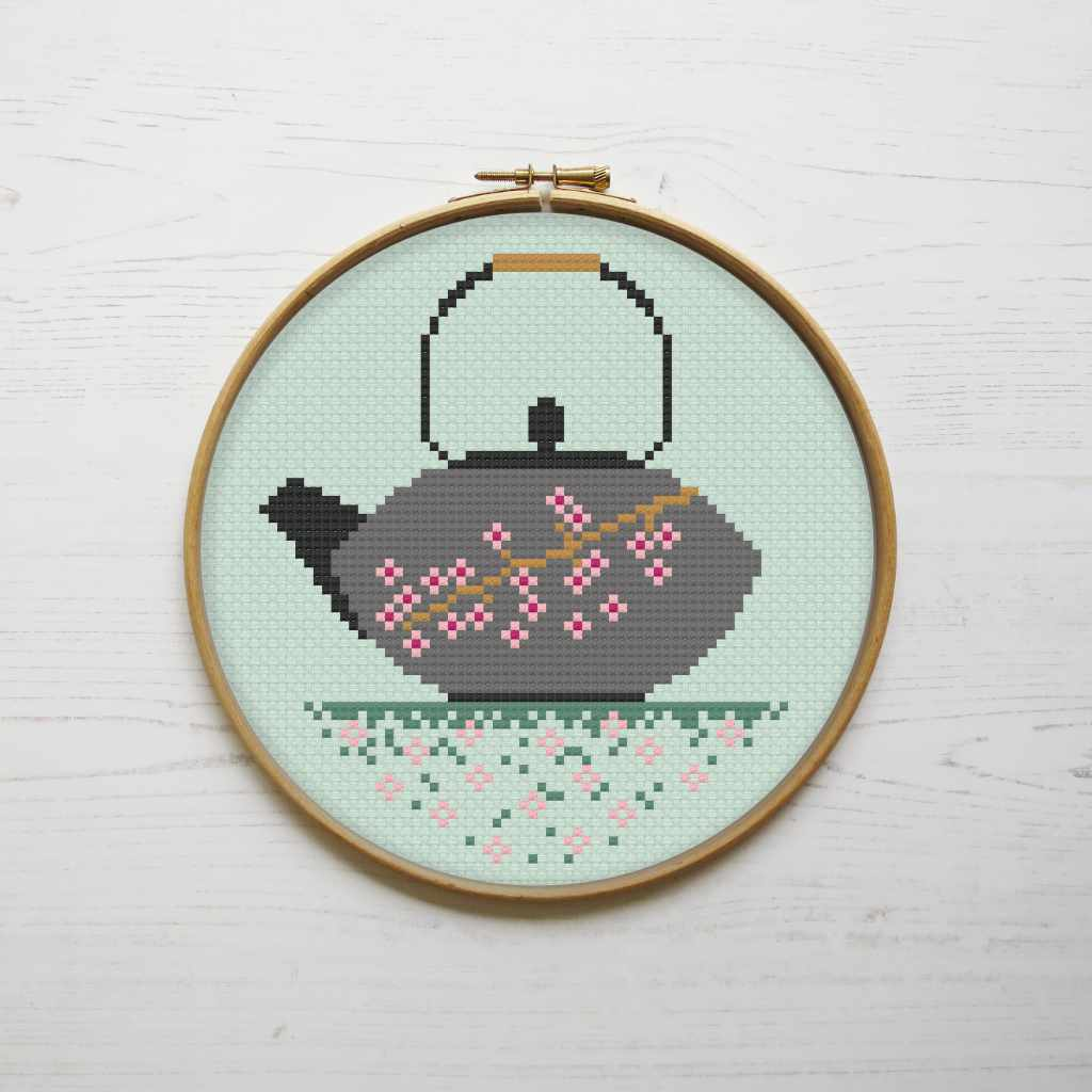 cross stitch pattern design in a hoop showing a teapot on a green background