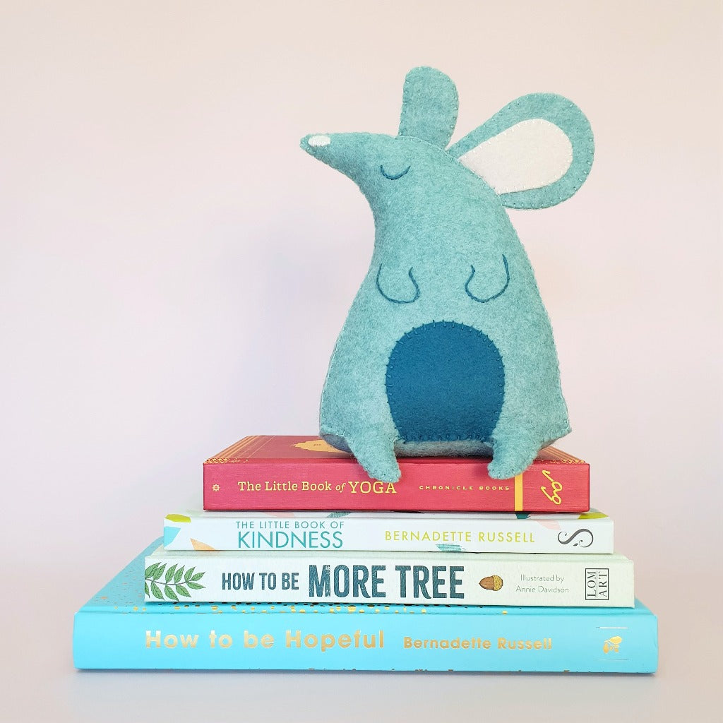 a hand sewn felt mouse sits on a pile of books