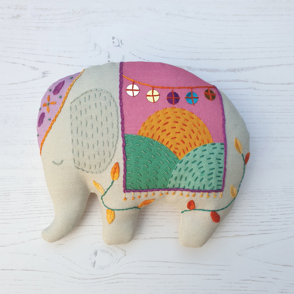 A stuffed elephant ornament, handmade and embellished with embroidery stitches and sequins.