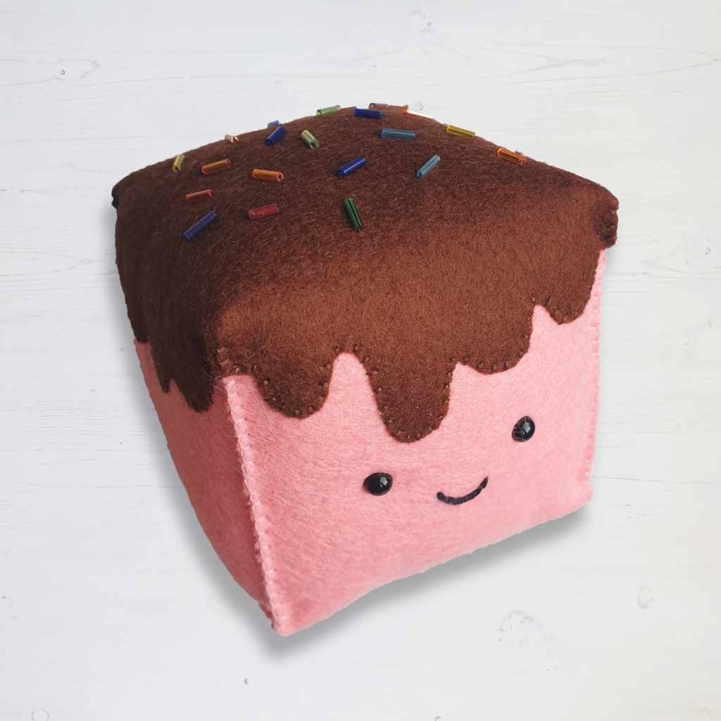 A pink felt marshmallow with chocolate brown topping and hand sewn sprinkles. Amigurumi style toy eyes, blanket stitch.