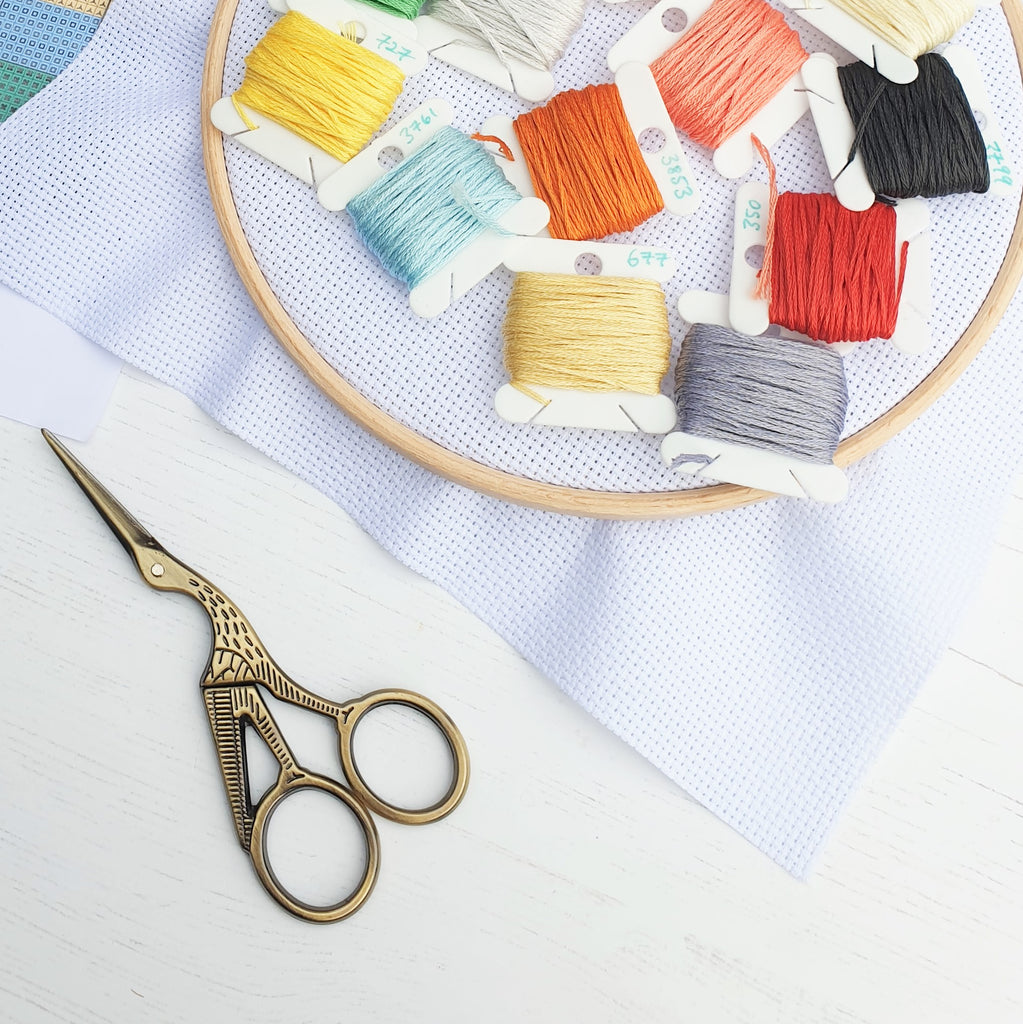 Colourful sewing bobbins wound with brightly coloured embroidery threads, resting on cross stitch fabric in a hoop, and also with a pair of stork sewing scissors.