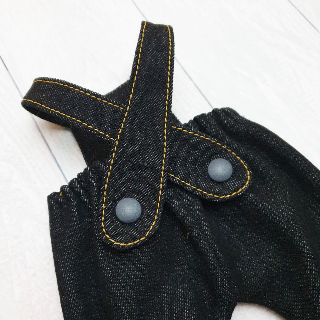 Denim detail of a pair of toy dungarees featuring gold topstitching and KAM snap fastening