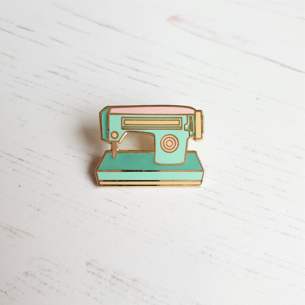 A hard enamel sewing machine pin badge, featuring and 1950s style sewing machine in mint greens and pink with gold plating.