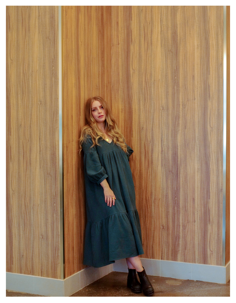 a blonde woman wearing a dark green forest dress in leaning against a tall wooden wall in a modern styled restaurant space