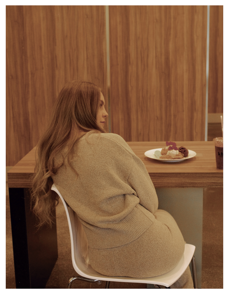 a blonde woman wearing a beige knit outfit sitting in a white chair in front of a table with a plate of waffles ready to eat.