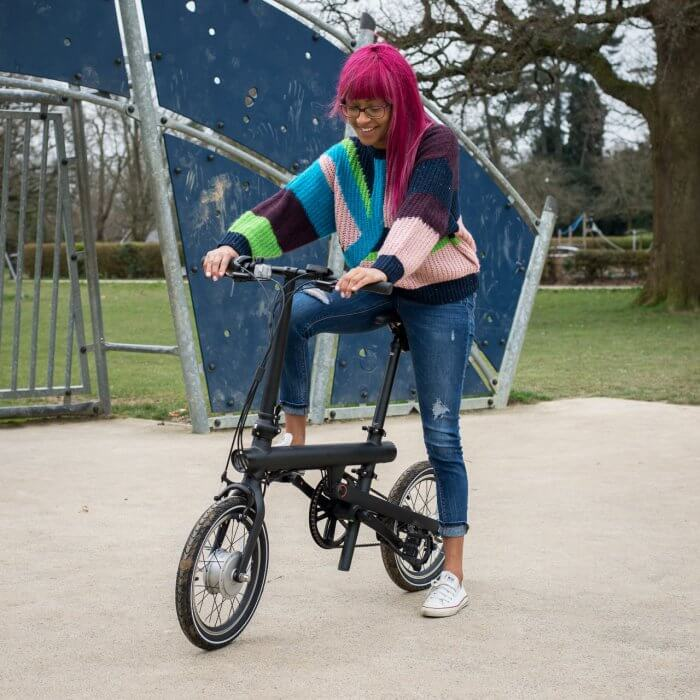 QiCycle electric folding bike stood astride smile