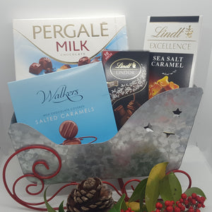 Chocolate overload hamper.  Great christmas hamper gift. Christmas sleigh decor in stainless steel in silver and red. Shared with the family but the kids will love this.