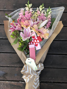 Pink bouquet. Valentine hamper of pink lilies and pink gerbera and chocolates. Milk chocolates wrapped in red and pink heart shapes design paper.
