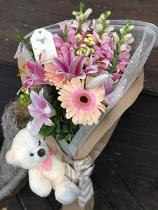 Bear cuddles. Valentine hamper of pink lilies and pink gerbera and white teddy bear stuff toy with pink ribbon.