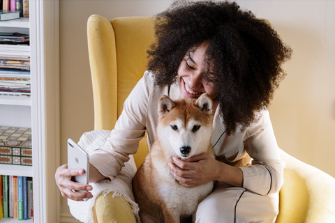 Woman smiling holding dog in arms