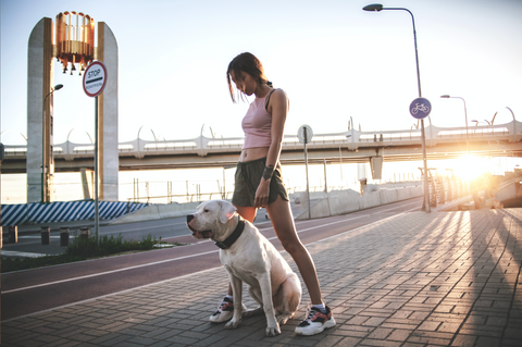 Woman posing holding dog in the city