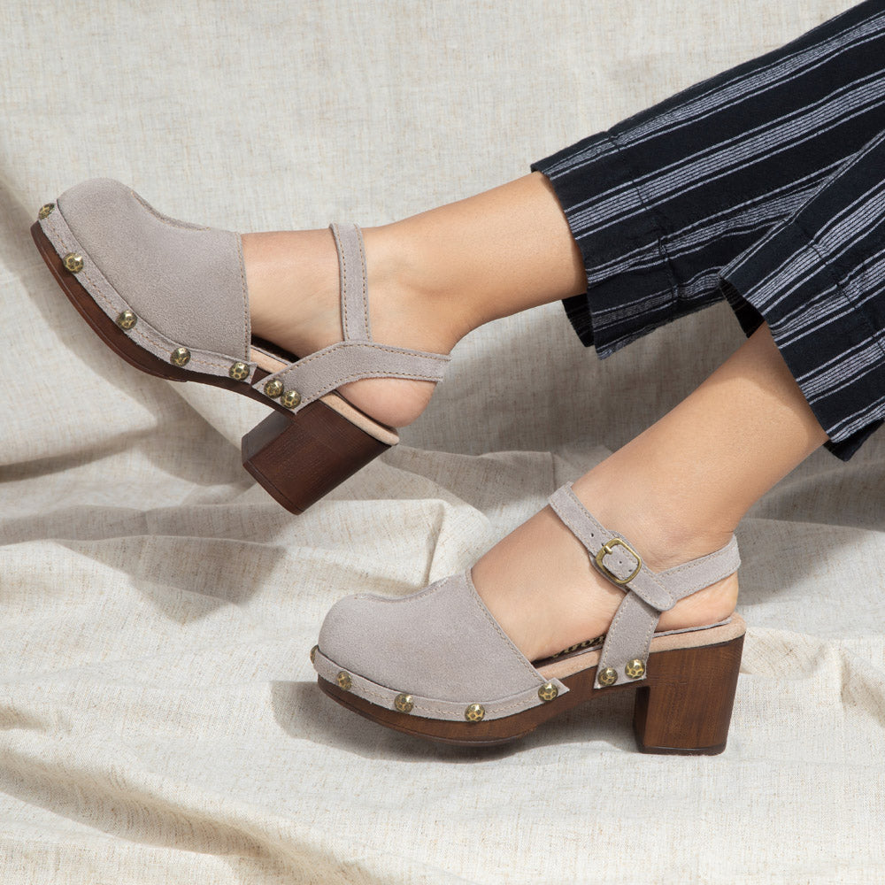 Betty closed-toe clog features a suede upper and buckled ankle strap.